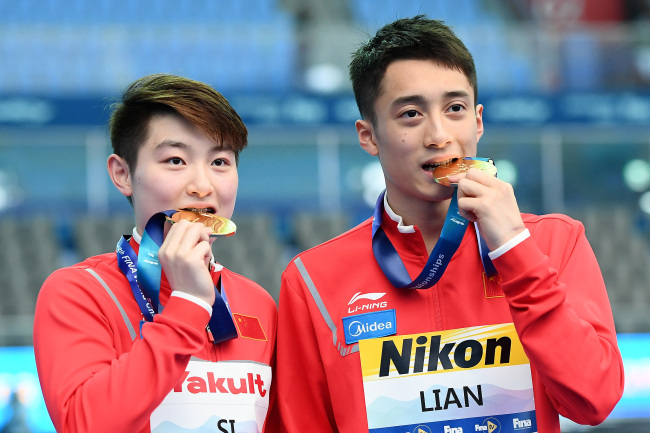 Gold medalists Yajie Si and Junjie Lian of China pose during the medal ceremony for the Mixed 10m Synchro Platform Final on day two of the Gwangju 2019 FINA World Championships at Nambu International Aquatics Centre on July 13, 2019 in Gwangju, South Korea. [Photo: VCG/Getty Images/Quinn Rooney]