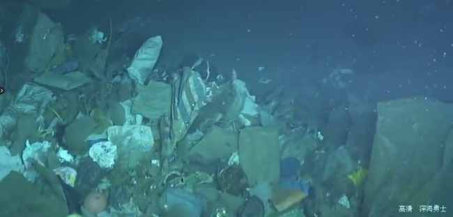 A large patch of garbage discovered by China's Deep Sea Warrior submarine about 2,000 meters underwater. [Screenshot: China Plus]