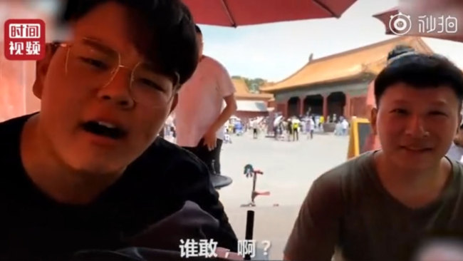 Two male tourists sit in a public rest area and smoke inside the Palace Museum in Beijing on Sunday, July 7, 2019. [Photo: Screenshot]