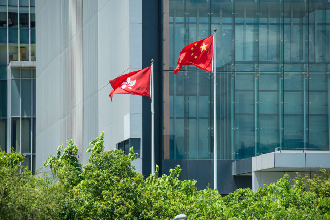 The national flag of China and the regional flag of the Hong Kong Special Administrative Region flutter in Hong Kong. [File photo: VCG]
