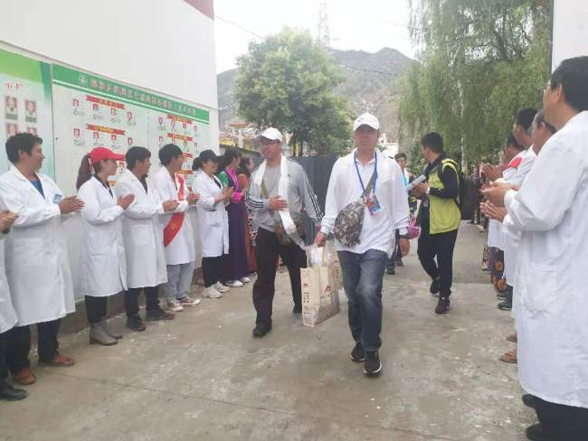 Medical professionals arrived at dispensary of Tuoding Township. Local people were waiting at the gate to welcome them. [Photo: China Plus]