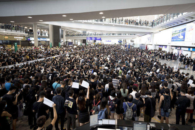 Protesters demonstrate at the airport in Hong Kong, Monday, August 12, 2019. [Photo: AP/Vincent Thian]