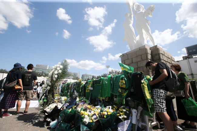 People put flowers, jerseys and scarves at the commemoration site for former Beijing Guoan forward Walter Martinez in front of Beijing Worker Stadium in Beijing on Aug 13, 2019. [Photo: IC]