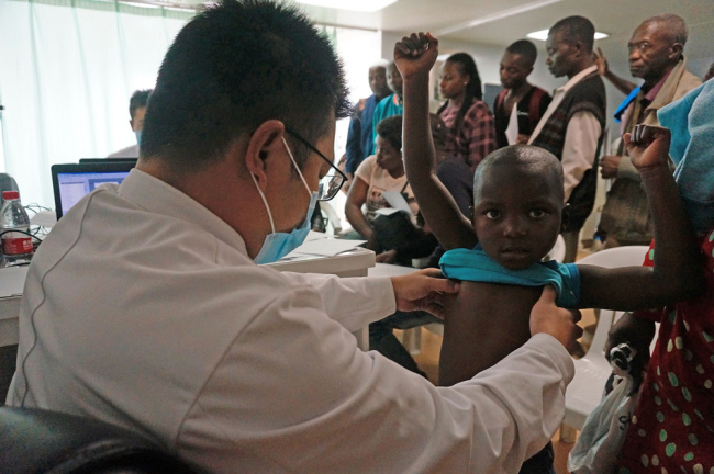 A doctor examines a child on Chinese naval hospital ship Peace Ark in Mozambique, on December 9, 2017. [File Photo: VCG]