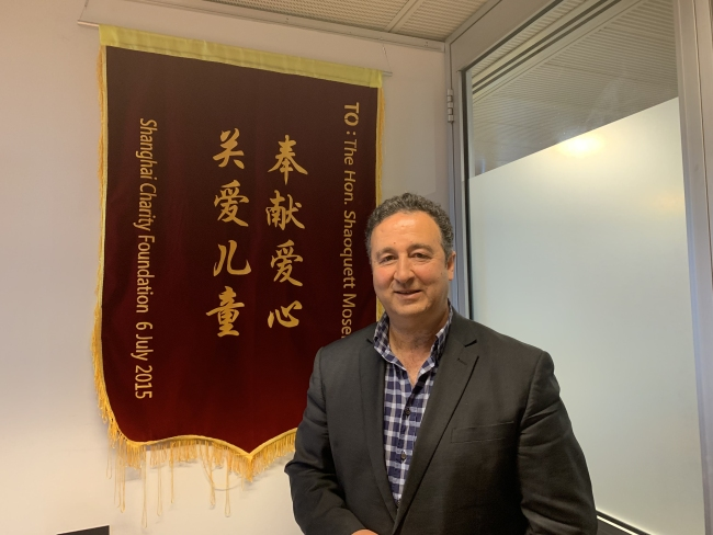 """Shaoquett Moselmane photographed here with a banner reads """"Contribution of a warm heart, Care for children"""" from the Shanghai Charity Foundation. [Photo: China Plus]"""