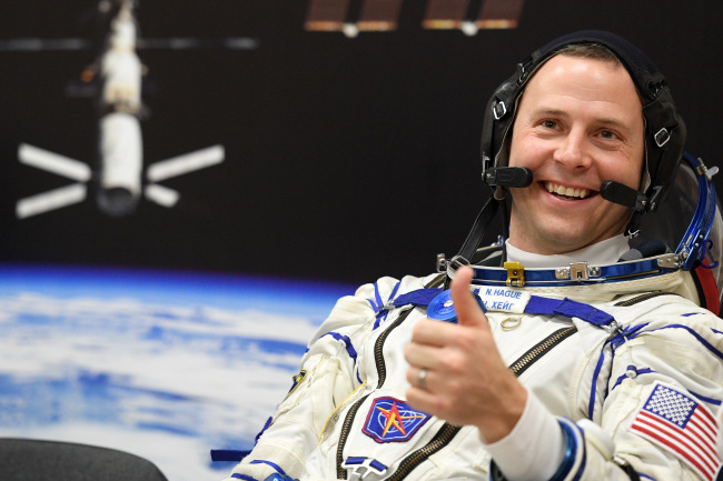 NASA astronaut Nick Hague, a member of the International Space Station (ISS) expedition 59/60, gestures shortly before the launch onboard the Soyuz MS-12 spacecraft from the Russian-leased Baikonur cosmodrome in Kazakhstan. [Photo: AFP/ Kirill KUDRYAVTSEV]