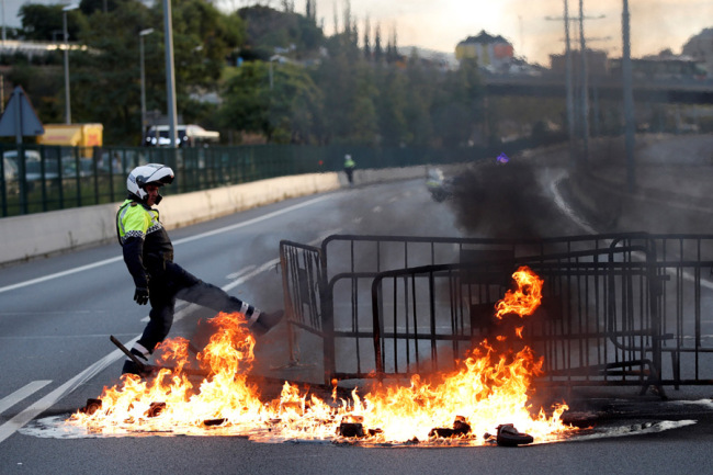 A policeman tries to extinguish a barricade on fire on a highway in Barcelona, Spain, October 18, 2019. [Photo: IC]