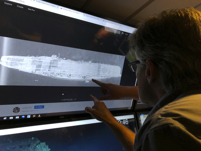 In this Wednesday, Oct. 16, 2019, photo, Vulcan Inc. director of subsea operations of the Petrel, Rob Kraft looks at images of the Japanese aircraft carrier Kaga, off Midway Atoll in the Northwestern Hawaiian Islands. Deep-sea explorers scouring the world's oceans for sunken World War II ships are honing in on a debris field deep in the Pacific. The research vessel called the Petrel is launching underwater robots about halfway between the U.S. and Japan in search of warships from the Battle of Midway. [Photo: AP/Caleb Jones]