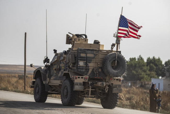 A Syrian woman and a child stand on the side of a road as a US military vehicle drives on a road after US forces pulled out of their base in the Northern Syriain town of Tal Tamr, on October 20, 2019. [Photo: AFP/Delil Souleiman]