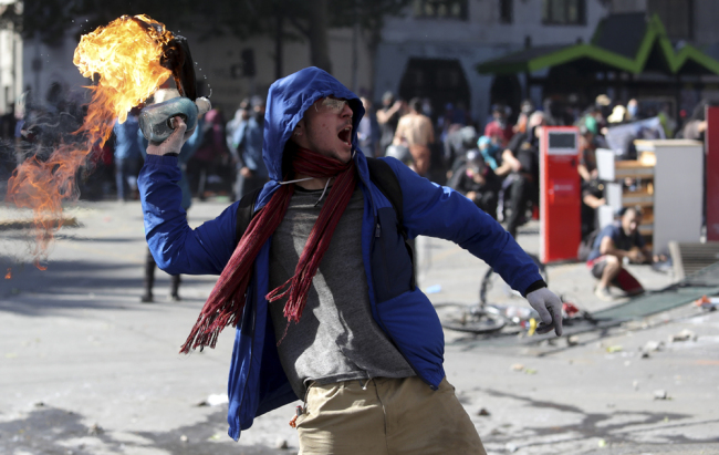 A protester throws a firebomb amid a march by students and union members in Santiago, Chile, Monday, Oct. 21, 2019. [Photo: AP/Miguel Arenas]