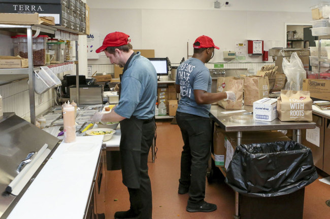 William Burns, left, general manager of the B.Good ghost kitchen inside Kitchen United's Chicago, Ill., location prepares food for delivery on Aug. 29, 2019. [Photo: AP]