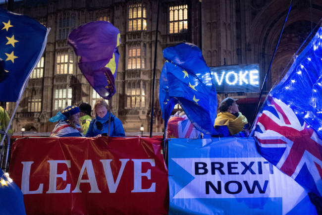 Pro and anti-Brexit protesters wave flags and hold banners as they demonstrate outside of the Houses of Parliament in central London on October 21, 2019. [Photo: AFP/Tolga Akmen]