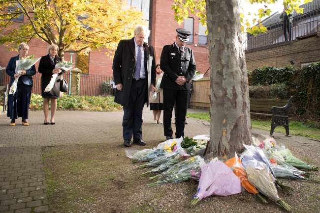 Britain's Prime Minister Boris Johnson stands with Chief Constable of Essex Police, Ben-Julian Harrington (R), after they laid flowers, during a visit to Thurrock Council Offices in Thurrock, east of London on October 28, 2019, following the October 23, 2019, discovery of 39 bodies concealed in a lorry. [Photo: AFP/POOL/Stefan Rousseau]