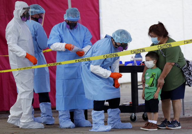 Jerry A. Mann, second from right, stands with his grandmother, Sylvia Rubio, as he prepares to be tested for COVID-19 by the San Antonio Fire Department at a free walk-up test site set up to help underserved and minority communities in San Antonio, Thursday, May 14, 2020. [Photo: AP]