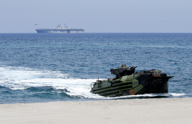 "US Navy's multipurpose amphibious assault ship USS WASP cruises in the background after dislodging AAVs (Amphibious Assault Vehicles), foreground, with American and Philippine troops on board during the Joint US-Philippine Military Exercise dubbed ""Balikatan 2019"" Thursday, April 11, 2019, off San Antonio, Zambales province northwest of Manila, Philippines. [File Photo: AP/Bullit Marquez]"