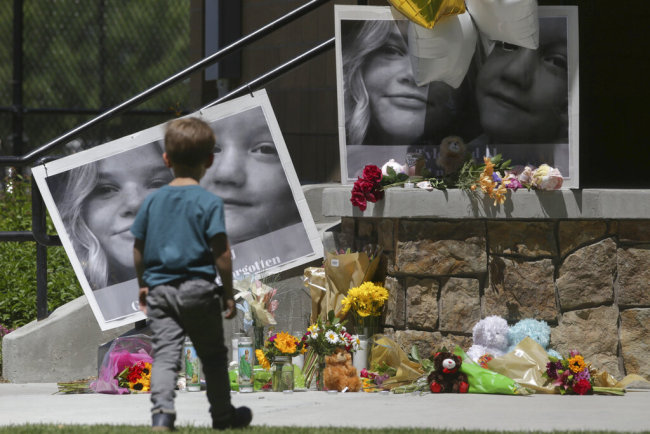 "In this June 11, 2020, file photo, a boy looks at a memorial for Tylee Ryan, 17, and Joshua ""JJ"" Vallow, 7, at Porter Park in Rexburg, Idaho. [Photo: AP]"